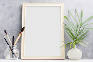 Large wooden Photo frame mock up with green palm leaves in vase and brushes in glass on shelf. Scandinavian style. Text space