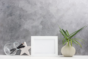 Photo frame mock up with plants in vase, ceramic star, pen and pencil in mason jar on shelf. Scandinavian style. Text space