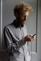A man listens to music on his headphones via his smartphone.