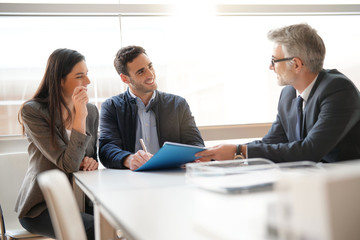 Young couple meeting financial advisor for home investment