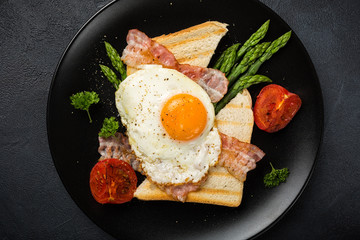 Breakfast or lunch with Fried egg, bread toast, green asparagus, tomatoes and bacon on black plate. Top view.