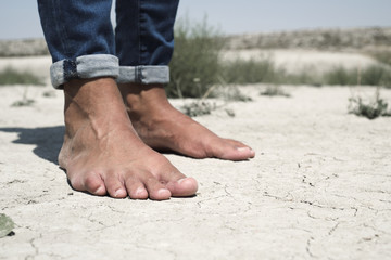 bare feet of a man on a cracked dry soil