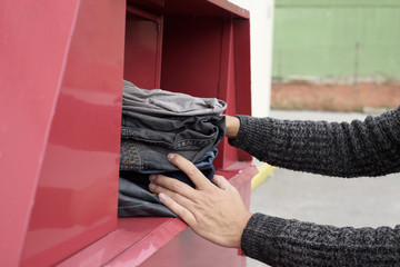 man depositing used clothes in a clothing bin