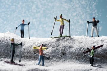 miniature skiers in a snowy landscape