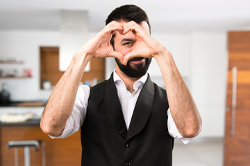 Cool man making a heart with his hands inside house