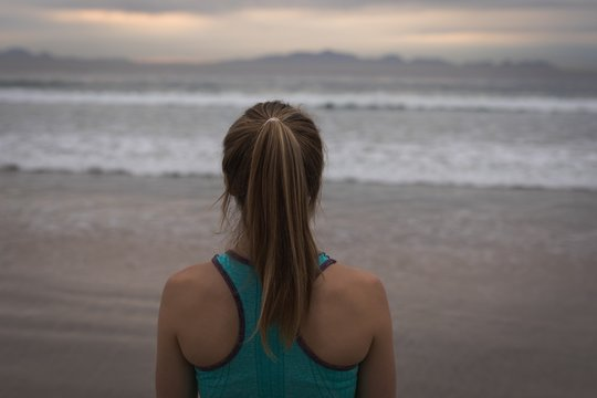 Woman in sports wear with ponytail standing at beachfront