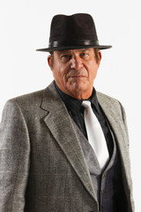 Older Man in Fine Gray Suit and Black Hat on White Background. An older gentleman in a fine gray suit in front of a plain, white background.