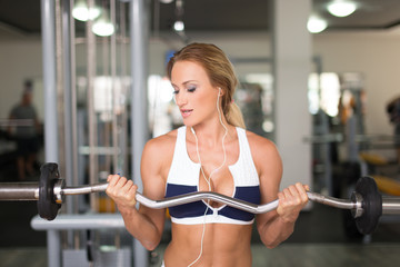 Young fintness model workout with olympic bar in gym