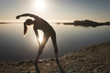 Woman performing stretching exercise near coast