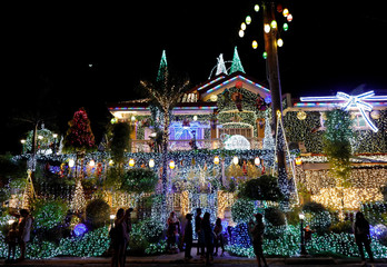 People take photos in front of a house lit up by christmas light installations in Rizal