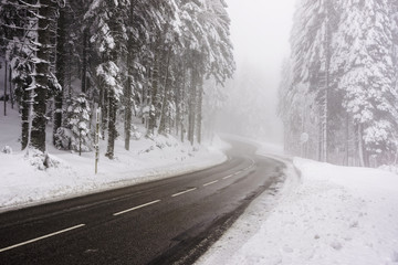 Road curve in wintry and foggy weather