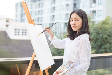 Asian Creative pensive painter thinking for paints a picture in workshop. Woman with artist concept.