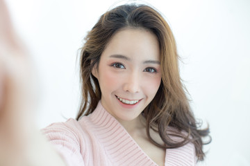 Attractive Asian Woman using smartphone for selfie with happy emotion, People lifestyle concept.