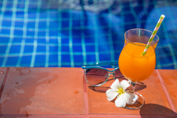 Fresh orange juice drink glass with flower and sunglasses on border of a swimming pool