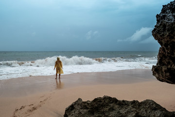 Young woman in yellow rain coat on the beach in heavy rain in Bali Indonesia