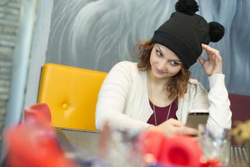 ragazza castana con cappellino pon pon giacchetta maglietta amaranto che si fà un selfie