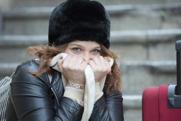 Ritratto di ragazza infreddolita con il colbacco nero e una valigia rossa - sfondo scale