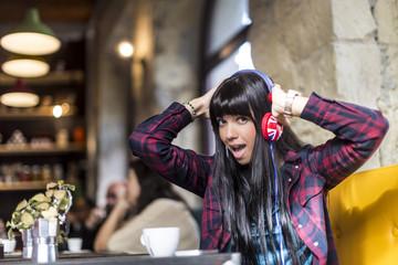 Ragazza mora con camicia a quadri ascolta divertita la musica con delle cuffie colorate dentro un bar .