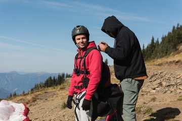 Man interacting with paraglider on mountain