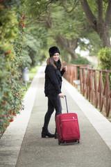 Turista con colbacco nero cammina sorridente con la sua valigia rossa in un parco