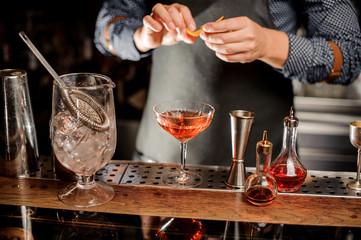 Barman making a fresh alcoholic cocktail with a fresh orange peel