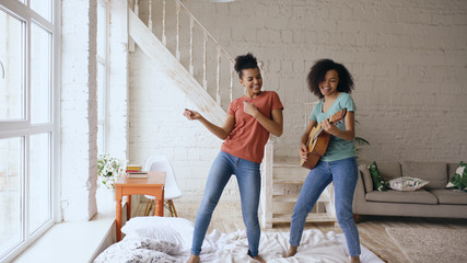 Mixed race young funny girls dancing singing and playing acoustic guitar on a bed. Sisters having fun leisure in bedroom at home