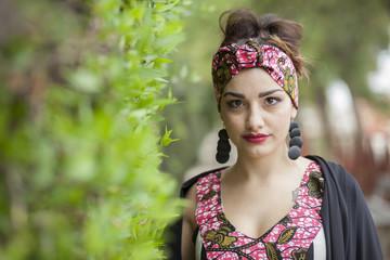 ragazza vestita molto colorata e fascia fantasia guarda seria  immersa in un bosco