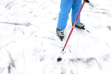 Outdoor Ice skating. Hockey player's legs and skates on ice rink.