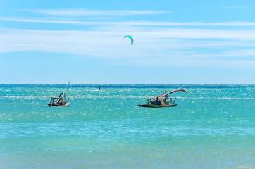 Jangada boat and kite surfers sailing together