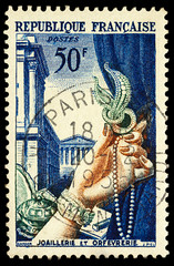 Female hand with jewelry on postage stamp
