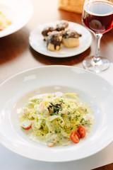 Italian food - fettuccine pasta and pesto sauce with seafood.