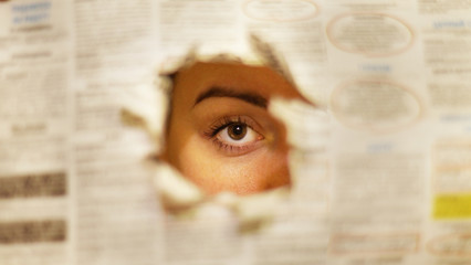 Ripped page of newspaper with articles and headlines. Young woman looks through the hole. The eye is in focus, the paper with news is blurred. Background texture