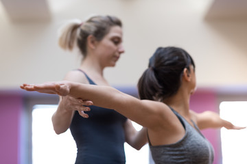 Yoga instructor and woman stretching arms