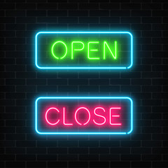 Neon green open and red close glowing signs in geometric shape on a brick wall background.