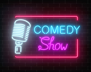 Neon comedy show sign with retro microphone on a brick wall background. Humor monolog glowing signboard.