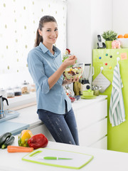 Smiling woman eating salad in the kitchen