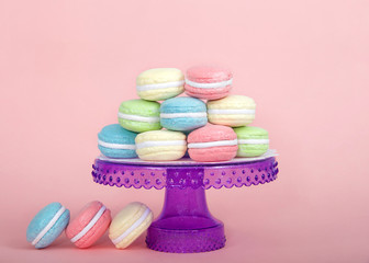 Large Macaroon cookies covered in granulated sugar on a table alternating colors stacked on a purple pedestal. Three cookies on the table. pink background. Popular pastry in France.