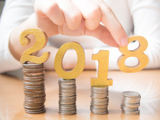 2018 New year saving money and financial planning concept. Female hands putting gold wooden number 2018 on stack of coins. Creative idea for business growth, tax payment, investment and banking.