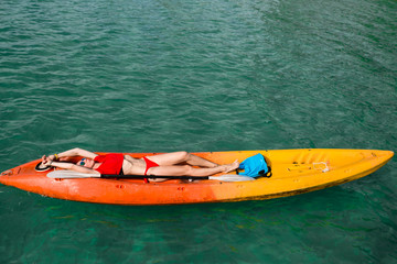 Brunette young woman girl in red bikini lying ,lie on red, orange, yellow kayak in the blue water. Asia. Thailand