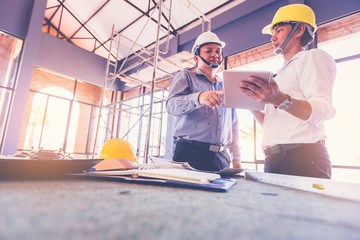 customer and constructor foreman worker with helmet and vest looking blueprints in new house building in real state business and housing industry concept. data in touch pad