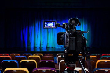 The LCD display on the camcorder. Shooting theatrical performances. The TV camera. Colorful chairs in the auditorium.