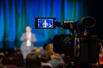 The LCD display on the camcorder. Shooting event. A man stands in front of an audience. The TV camera.
