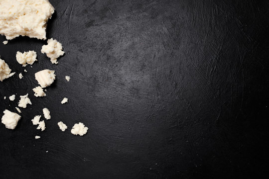 preparation of crumbling feta cheese for a salad on dark background. farming industry. milk products. gourmet food. free space concept