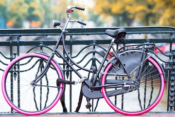 Pink bike on the bridge in Amsterdam, Netherlands. Beautiful view of canals in autumn