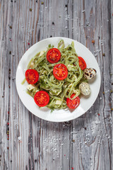 pasta from green spinach with mozzarella, greens and French mustard, quail eggs and cherry tomatoes on a plate, bell pepper and large sea salt on a gray wooden table on a dark background