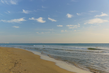 The sloping sandy beach of the sea. Calm. Clear sky, altocumulus clouds (lat. Altocumulus)
