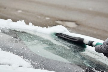 Зима. Очистка снега со стекла легкового автомобиля