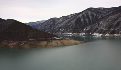 Huge lake with green flat water and grey with brown mountains landscape, picturesque view in Georgia country