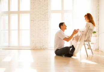 husband sitting on the floor, pregnant woman on a chair. The husband looks affectionately at his wife