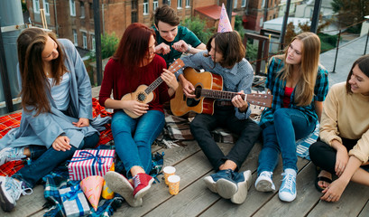 Group of friends listen to buskers singing and playing guitar and ukulele at a roof top party. Musician artistic lifestyle. Teenagers leisure